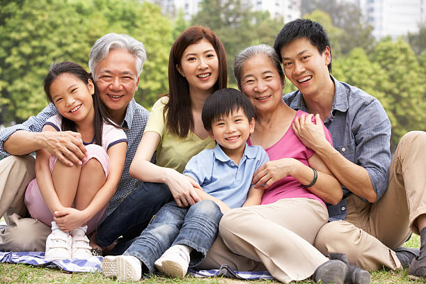 portrait of multi-generation chinese family relaxing in park - east asian ethnicity stock photos and pictures