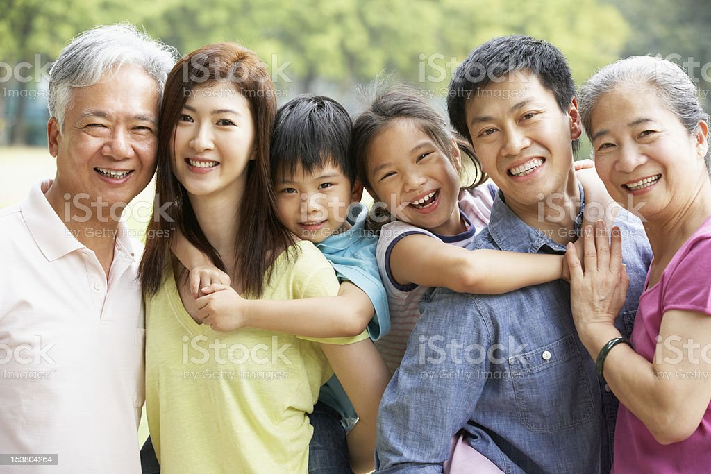 Portrait Of Multi-Generation Chinese Family Relaxing In Park Tog stock photo