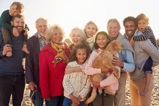 portrait of multi-generation family group with dog on winter beach vacation - generazioni foto e immagini stock