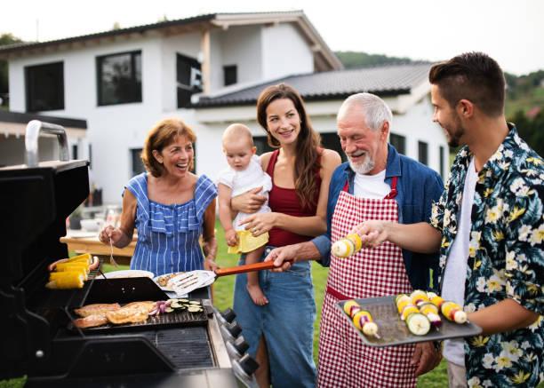 portret wielopokoleniowej rodziny na świeżym powietrzu na grillu ogrodowym, grillowaniu. - grillowany zdjęcia i obrazy z banku zdjęć