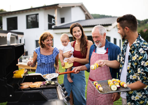 portrait of multigeneration family outdoors on garden barbecue, grilling. - family gatherings stock pictures, royalty-free photos & images