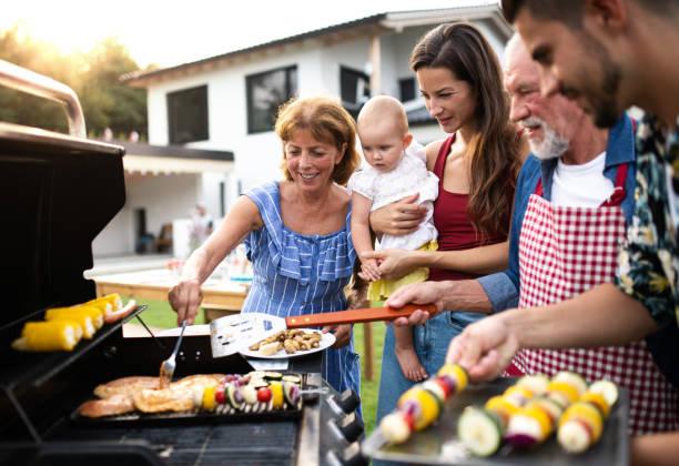 retrato de familia multigeneración al aire libre en barbacoa jardín, parrillas. - grilling fotografías e imágenes de stock