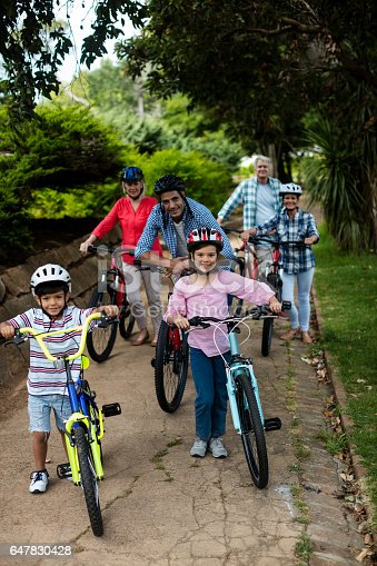 853720192 istock photo Portrait of multi-generation family standing with bicycle in park 647830428