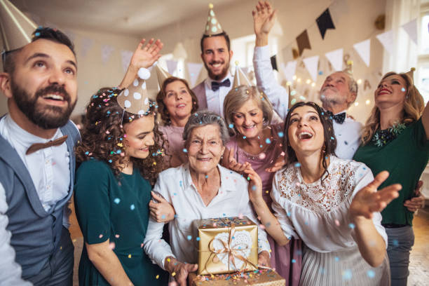 A portrait of multigeneration family with presents on a indoor birthday party. stock photo