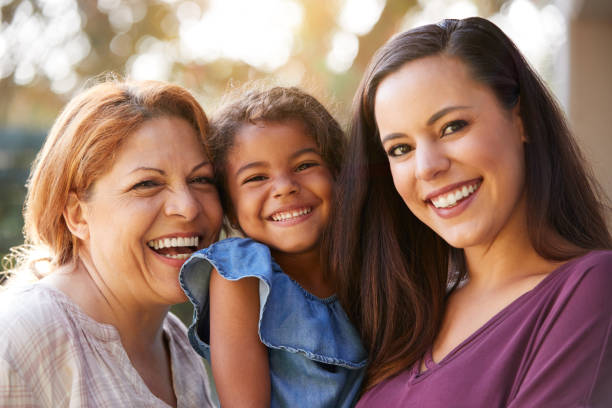 Portrait Of Multi-Generation Female Hispanic Family In Garden Smiling At Camera stock photo