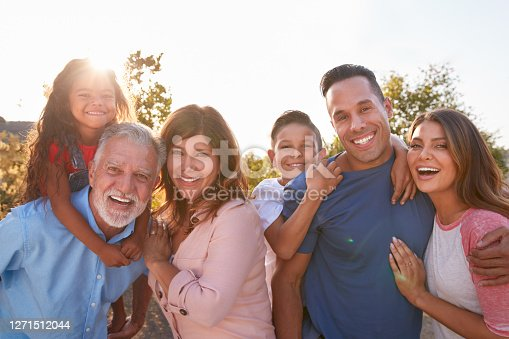 istock Portrait Of Multi-Generation Hispanic Family Relaxing In Garden At Home Together 1271512044