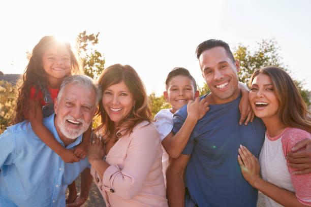 Portrait Of Multi-Generation Hispanic Family Relaxing In Garden At Home Together stock photo