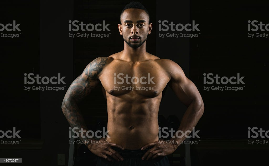 Portrait of Muscular African American Man Flexing Muscles in Gym stock photo