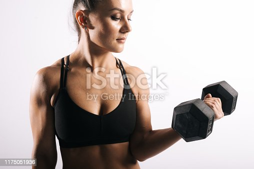 Portrait of muscular fitness woman with perfect athletic body in sports black bra holding dumbbells in strong hand. Shooting in professional studio on white isolated background
