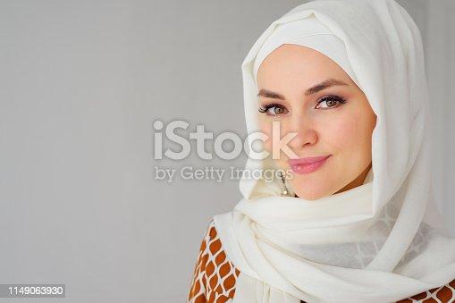 Portrait of beautiful young muslim arabian woman wearing white hijab looking at camera, copy space