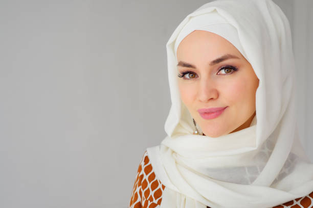 Portrait of muslim arabian woman wearing hijab, looking at camera Portrait of beautiful young muslim arabian woman wearing white hijab looking at camera, copy space religious veil stock pictures, royalty-free photos & images