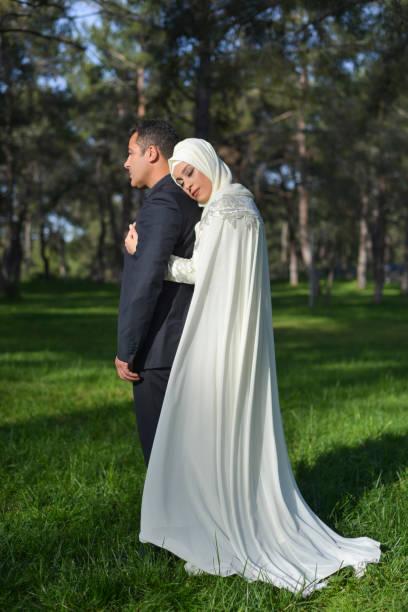 verticale de couples musulmans de mariée et de marié posant dans un stationnement public - mariage musulman photos et images de collection