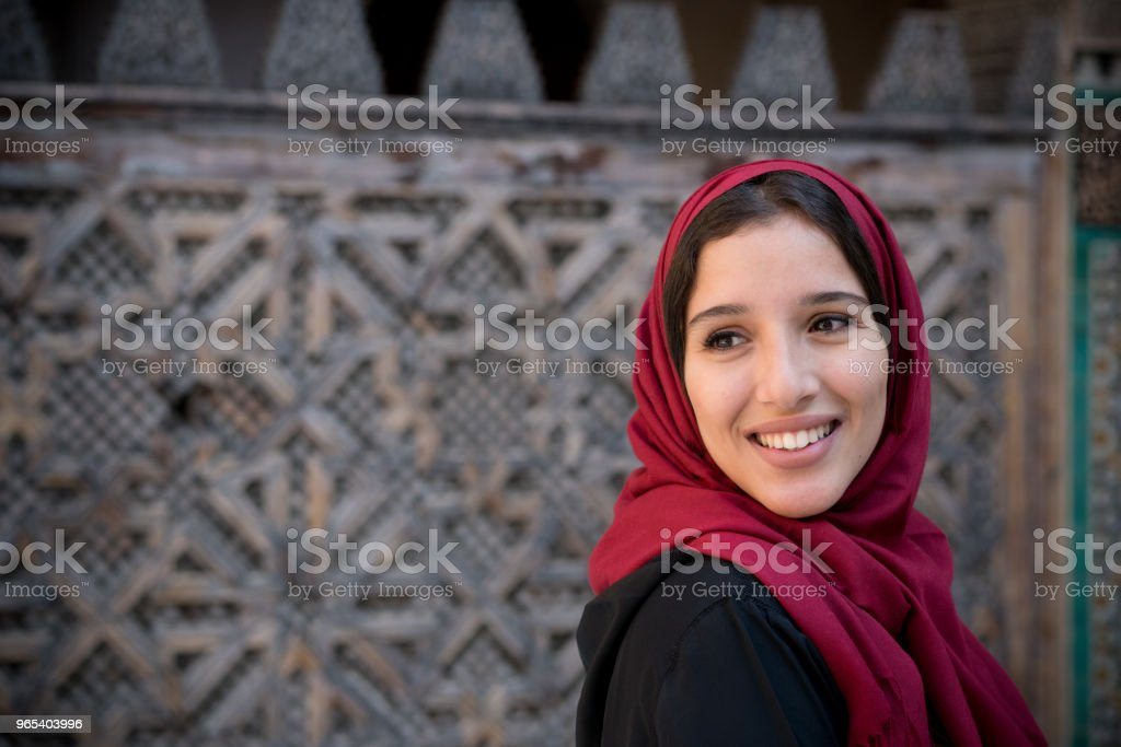 Portrait of muslim woman smiling in traditional clothing with red hijab royalty-free stock photo