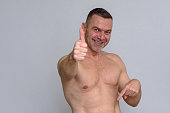 istock Portrait of naked mature man giving thumbs up 932859876