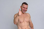 istock Portrait of naked mature man giving thumbs up 932867788