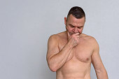 istock Portrait of naked mature man looking concerned 932846932