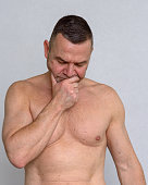 istock Portrait of naked mature man looking concerned 932872618