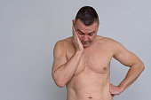 istock Portrait of naked mature man looking fed up 932856626