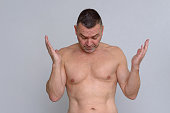 istock Portrait of naked mature man looking frustrated 932846226