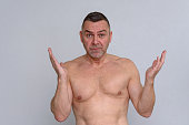 istock Portrait of naked mature man looking frustrated 932876950