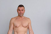 istock Portrait of naked mature man looking frustrated 932895830