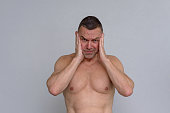 istock Portrait of naked mature man looking stressed 932870522