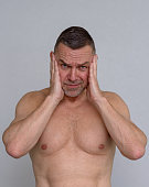 istock Portrait of naked mature man looking stressed 932880824