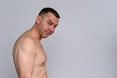 istock Portrait of naked mature man looking unimpressed 932891586