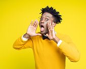 Portrait of nerdy young man shouting against yellow background