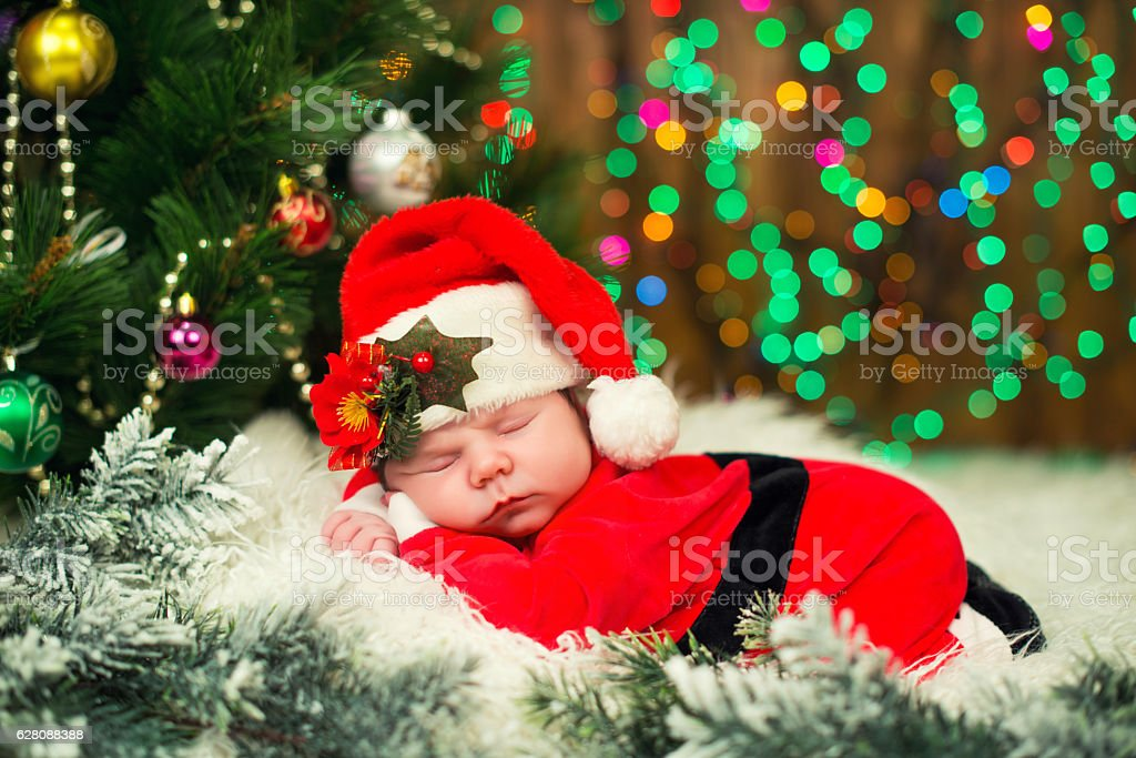 Portrait of newborn baby in santa clothes lying under christmas royalty free stock photo