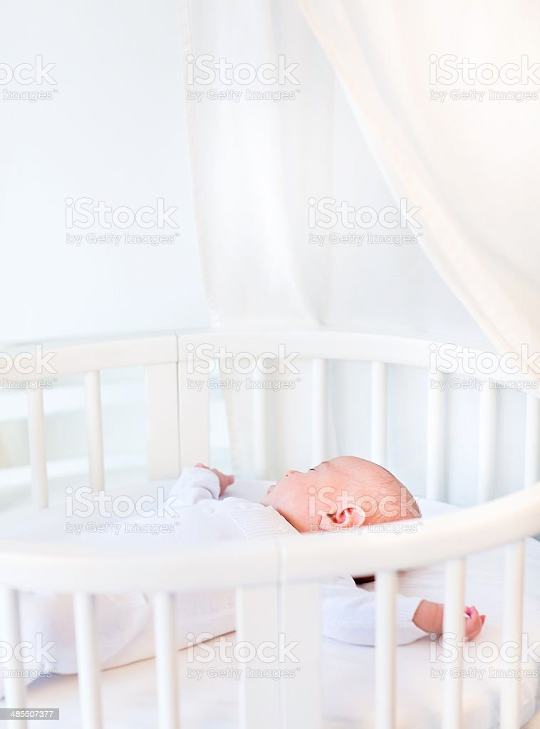 Portrait of newborn baby in white round crib with canopy stock photo