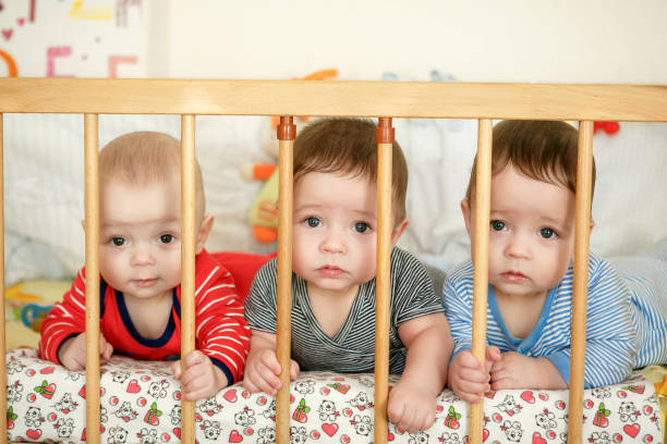 portrait of  newborn triplets in the bed - triplets stock photos and pictures