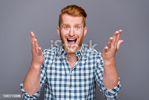 1092211952 istock photo Portrait of nice amazed astonished emotional handsome attractive trendy man wearing checkered shirt showing hands gesture opened mouth isolated over grey pastel background 1092210396