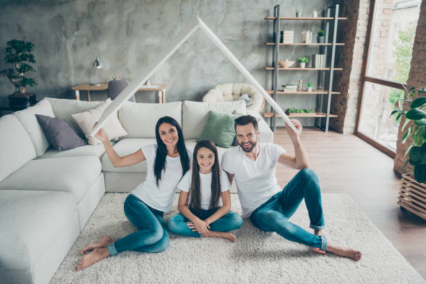 Portrait of nice attractive cheerful family wearing casual white t-shirts jeans sitting on carpet floor holding in hand roof investment at industrial loft style interior living-room cozy comfort Portrait of nice attractive cheerful family wearing casual white t-shirts, jeans sitting on carpet floor holding in hand roof investment at industrial loft style interior living-room cozy comfort home insurance stock pictures, royalty-free photos & images