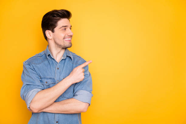 Portrait of nice attractive content cheerful cheery guy pointing forefinger aside advert copy empty black place space follow subscribe isolated over bright vivid shine vibrant yellow color background stock photo