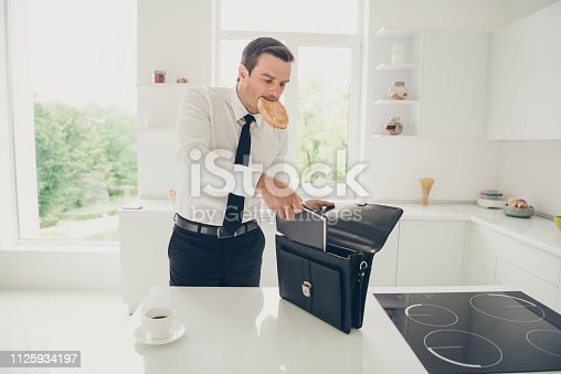 Portrait of nice attractive handsome focused concentrated serious man diplomat business shark keeping snack in mouth preparing to work day at light modern interior kitchen