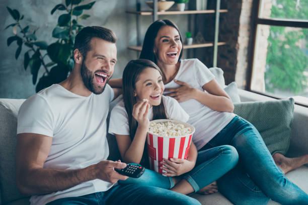 Porträt von schönen attraktiven schöne positive fröhliche fröhliche Familie trägt lässige weiße T-Shirts Jeans Jeans Jeans sitzend auf dem Sofa mit Spaß beim Anschauen lustige Video genießen Freizeit genießen – Foto