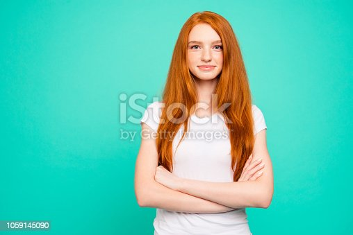 istock Portrait of nice calm content positive peaceful cute bright vivid shiny red straight-haired girl in casual white t-shirt, folded hands, isolated over turquoise green background 1059145090
