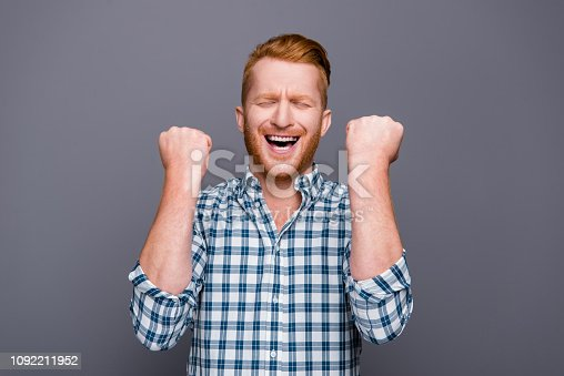istock Portrait of nice cheerful cheery astonished handsome attractive man wearing checkered shirt opened mouth holding fists isolated over grey pastel background 1092211952