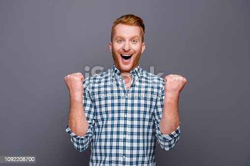 1092211952 istock photo Portrait of nice cheerful cheery funny handsome attractive man with beard stubble bristle wearing checkered shirt opened mouth celebrating winning isolated over grey pastel background 1092208700