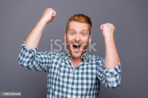 1092211952 istock photo Portrait of nice cheerful cheery lucky astonished handsome attractive man wearing checkered shirt opened mouth raising fists isolated over grey pastel background 1092205446