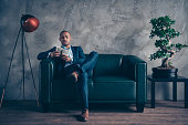 Portrait of nice classy chic elegant attractive content busy guy wearing jacket suit executive manager masculine sitting on couch account sum budget at workplace station gray concrete wall.