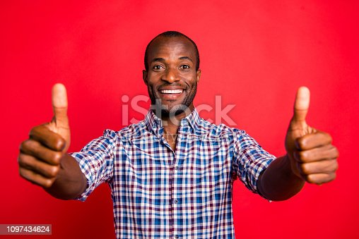 Portrait of nice cool handsome attractive cheerful positive guy wearing checked shirt showing double thumb-up isolated over bright vivid shine red background