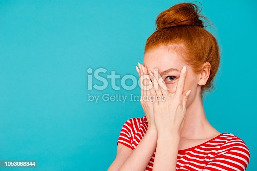 Portrait of nice cute attractive magnificent lovely cheerful red-haired girl with bun,hiding face behind fingers, peeking, empty place, copy space, isolated on bright vivid blue background
