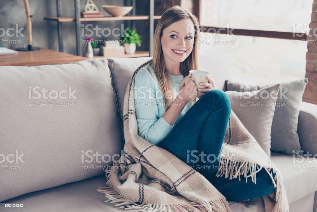 Portret van mooie, leuke, positieve vrouw met kopje koffie in handen, vallende plaid, op zoek naar de kant, zitten thuis in de woonkamer, genieten van het weekend - Royalty-free Alleen volwassenen Stockfoto