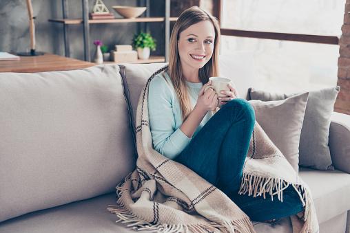 Portret Van Mooie Leuke Positieve Vrouw Met Kopje Koffie In Handen Vallende Plaid Op Zoek Naar De Kant Zitten Thuis In De Woonkamer Genieten Van Het Weekend Stockfoto en meer beelden van Alleen volwassenen