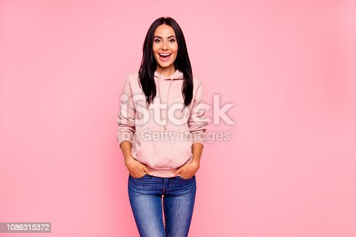 Portrait of nice excited sweet lovely attractive adorable winsome charming cheerful cheery glad girl holding hands in pockets isolated over pastel pink background