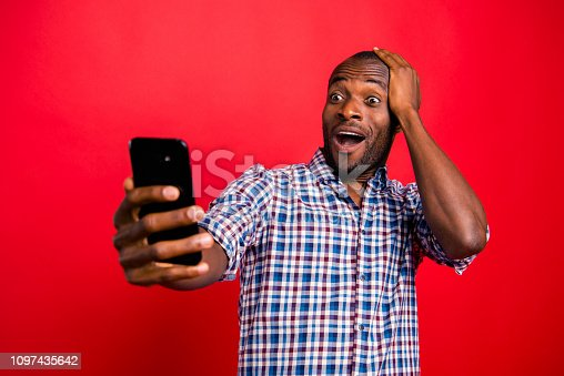 istock Portrait of nice funny crazy handsome attractive cheerful guy wearing checkered shirt holding in hands cell reading gadget device isolated over bright vivid shine red background 1097435642