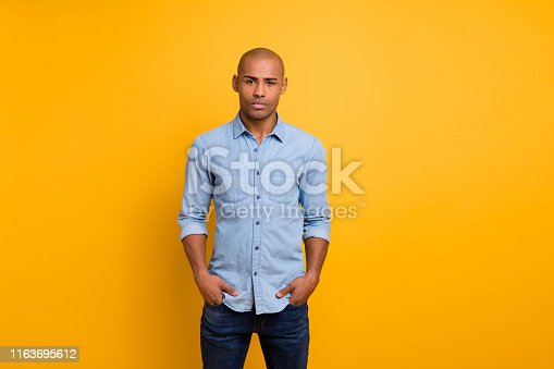 1163696387 istock photo Portrait of nice guy hands pockets look isolated over yellow background 1163695612