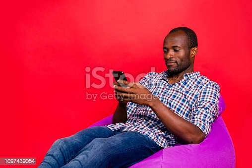 istock Portrait of nice handsome cheerful guy wearing checkered shirt sitting on violet purple bag using application roaming isolated over bright vivid shine red background 1097439054